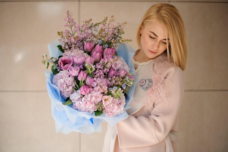 Flicka i laget som rymmer en bukett av purpurfärgade violetta tulpan och lilan royaltyfri fotografi