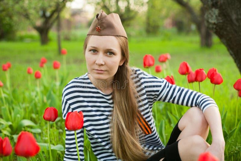 Flicka i likformig av det stora patriotiska kriget Krigaresammanträde på gräset mellan blommor Flicka som bär gröna dräkter av vä royaltyfria foton