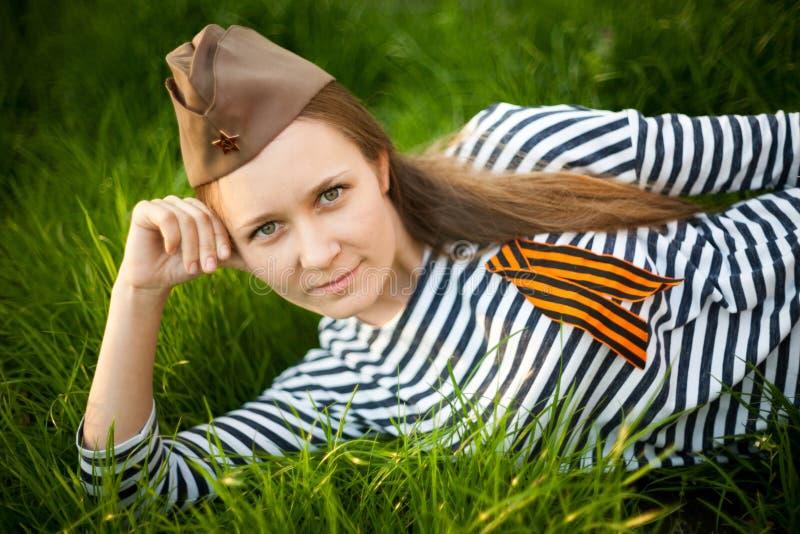 Flicka i likformig av det stora patriotiska kriget Krigaresammanträde på gräset mellan blommor Flicka som bär gröna dräkter av vä fotografering för bildbyråer