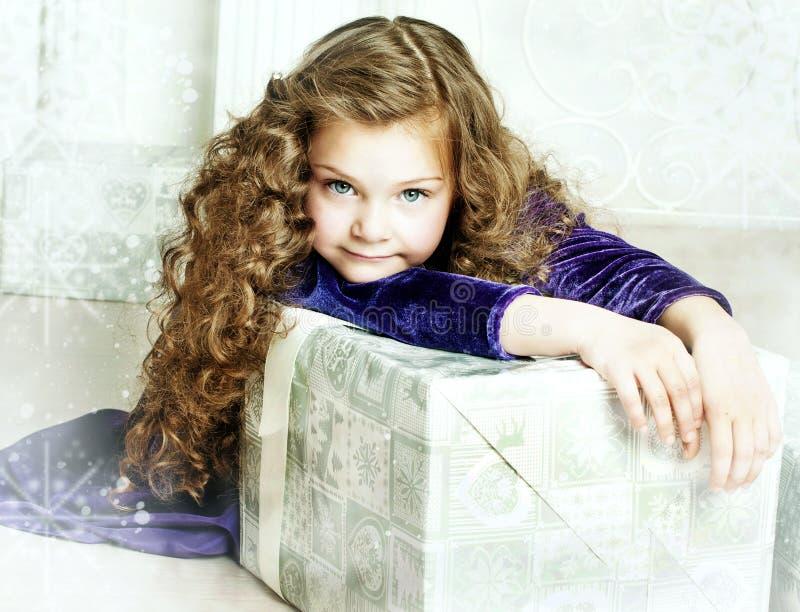 Flicka i lilaklänningen som rymmer en gåva royaltyfria bilder