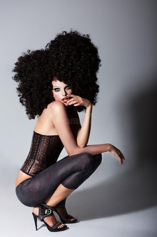Flicka i lockig fantastisk peruk. Burrig frisyr royaltyfria foton
