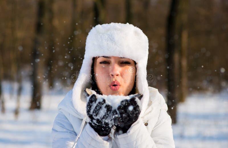 Flicka i parkera i vinter som blåser snöflingor royaltyfri foto