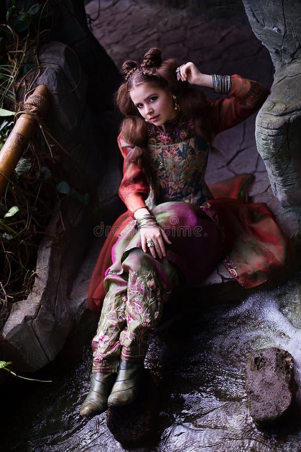 Flicka i person som tillhör en etnisk minoritetkläder i tropisk trädgård royaltyfri fotografi