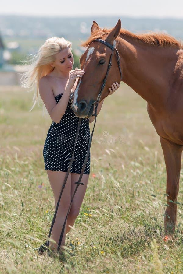 Flicka i prickklänning med den bruna hästen royaltyfri bild