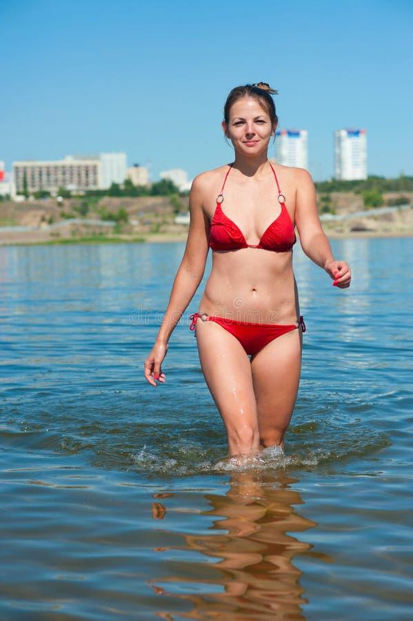 Flicka i röd bikiniutgång från floden arkivbild