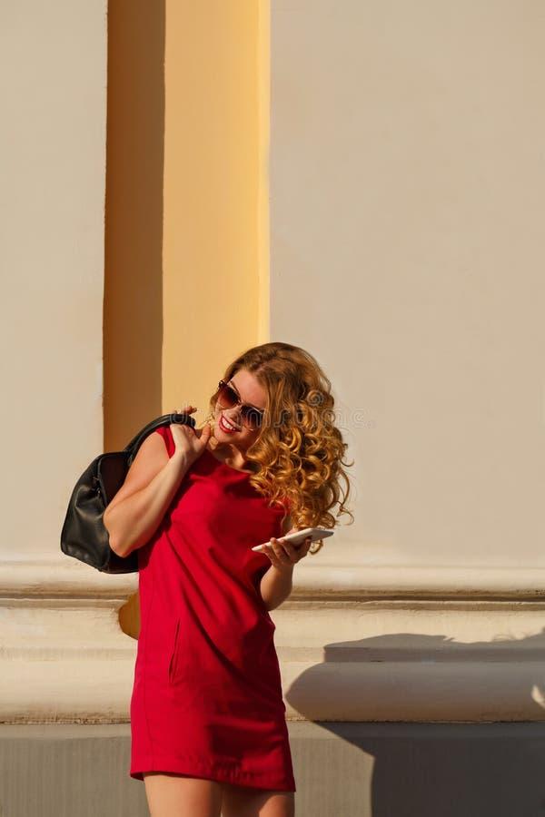 Flicka i röd klänning och med den moderiktiga handväskan, telefon royaltyfri foto