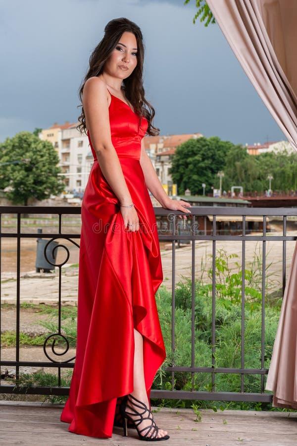 Flicka, i röd klänninginnehavklänning och uppvisning av av hennes ben och skor på trädgårdbalkongen arkivfoton