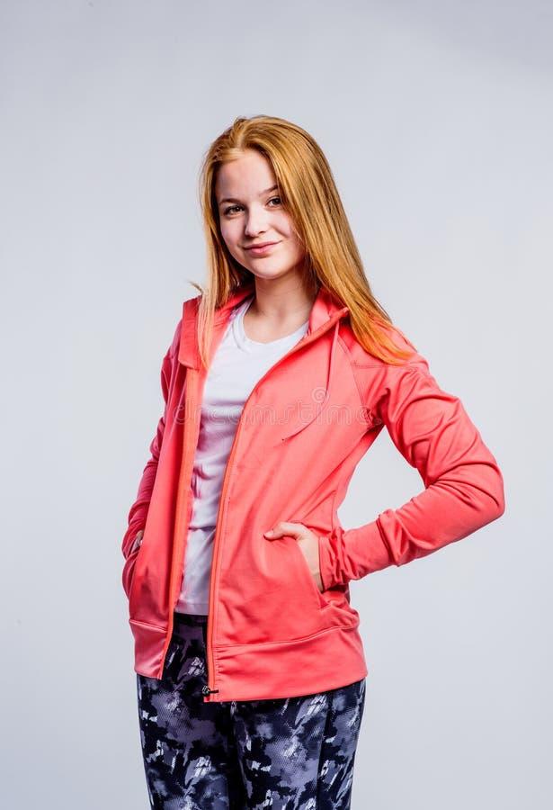 Flicka i röd tröja- och konditiondamasker, studioskott fotografering för bildbyråer