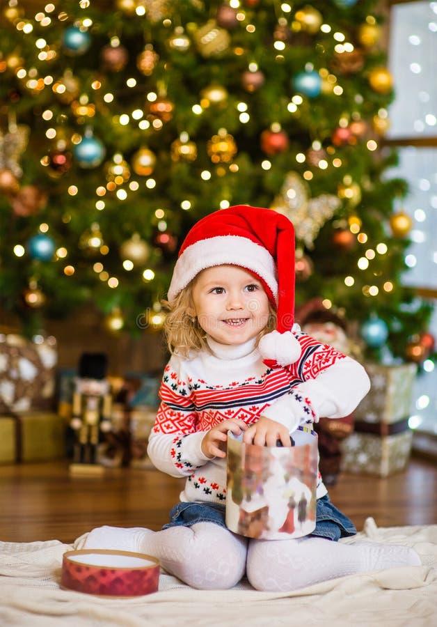 Flicka i röda gåvor för santa hattöppning nära en julgran royaltyfri fotografi