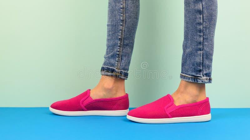 Flicka i röda gymnastikskor och riven sönder jeans som går på det blåa golvet Sportstil royaltyfria foton