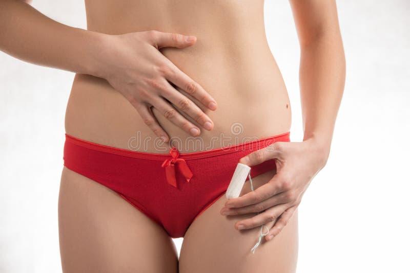 Flicka i röda kortslutningar rymma hygieniska tamponger och block under mig royaltyfria bilder