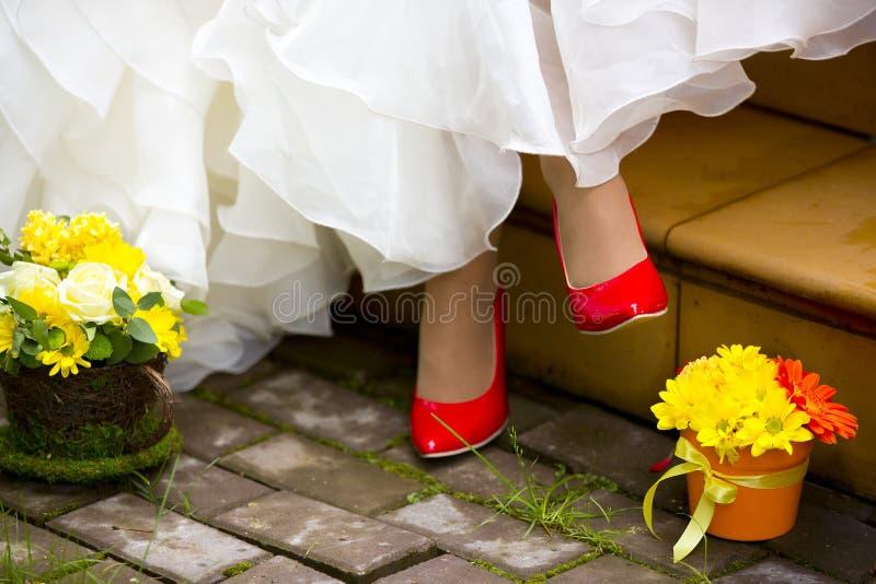 Flicka i röda skor, den vita bröllopsklänningen och två blomkrukor arkivbilder