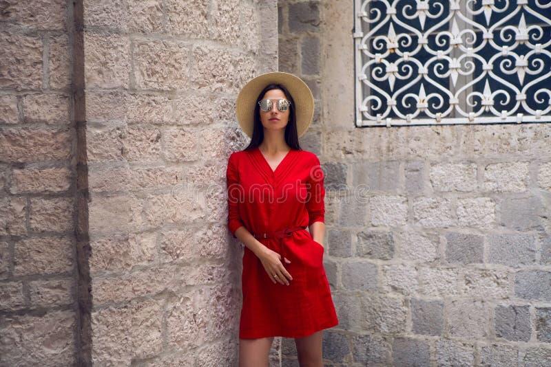 Flicka i rött klänninganseende på stenväggen av slotten arkivfoton