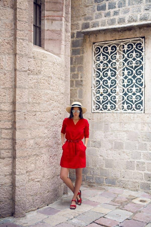 Flicka i rött klänninganseende på stenväggen av slotten arkivbild