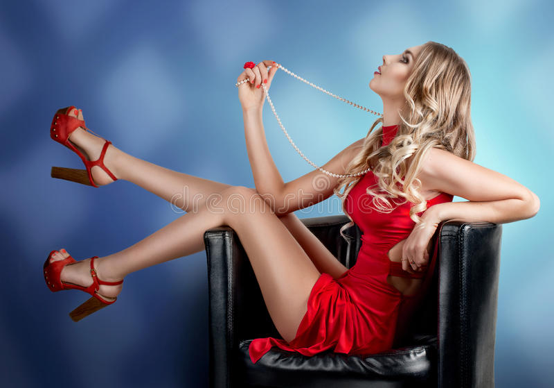Flicka i rött klänningsammanträde på en stol med din fot royaltyfri foto
