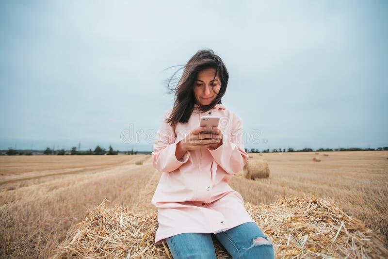Flicka i regnrock Flicka för höstståendehipster i ett lag Kvinna som använder telefonen royaltyfria bilder