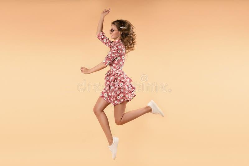 Flicka i rosa blom- klänning som hoppar och skrattar i studio arkivfoton