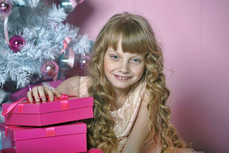 Flicka i rosa färger på julgranen royaltyfri foto