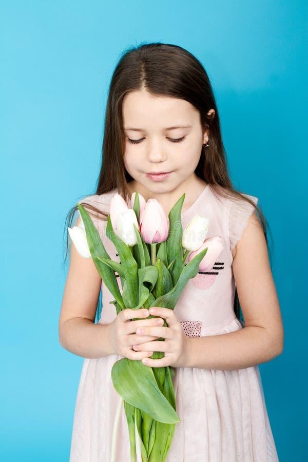 Flicka i rosa färgklänning med tulpan fotografering för bildbyråer