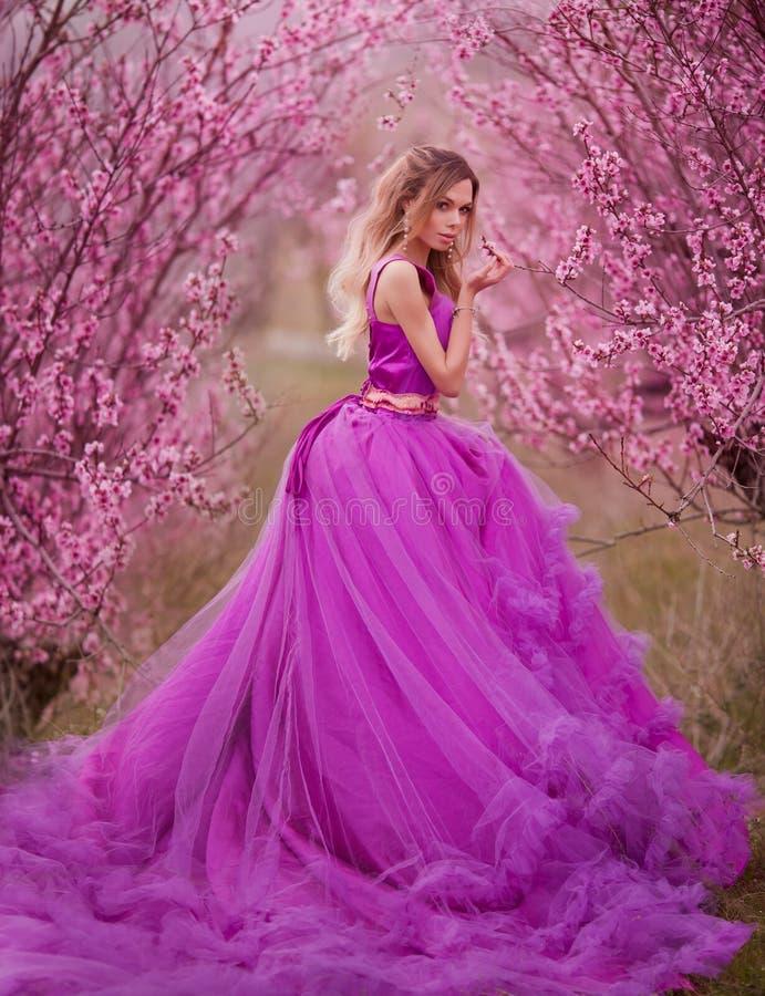 _flicka i rosa klänning i blomma trädgård arkivfoto