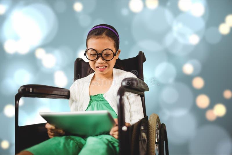 Flicka i rullstol genom att använda den digitala minnestavlan arkivbild