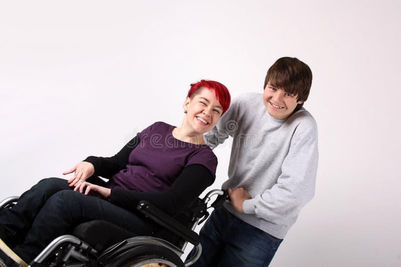 Flicka i rullstol med hjälpredan royaltyfri bild