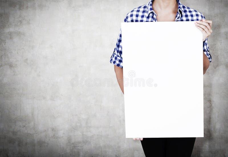 Flicka i rutig skjorta med affischen nära betongväggen arkivfoton