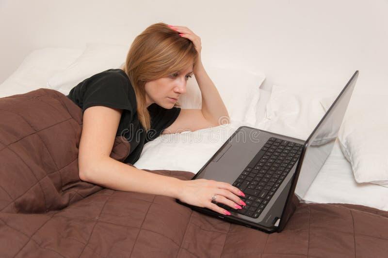 Flicka i säng med bärbara datorn fotografering för bildbyråer