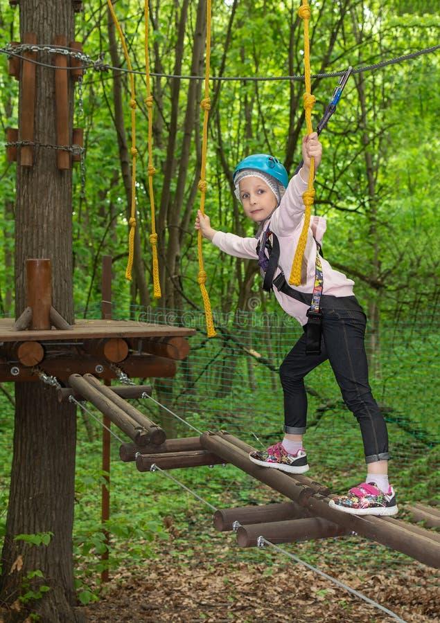 Flicka i selekorsning repbro i skog royaltyfri bild