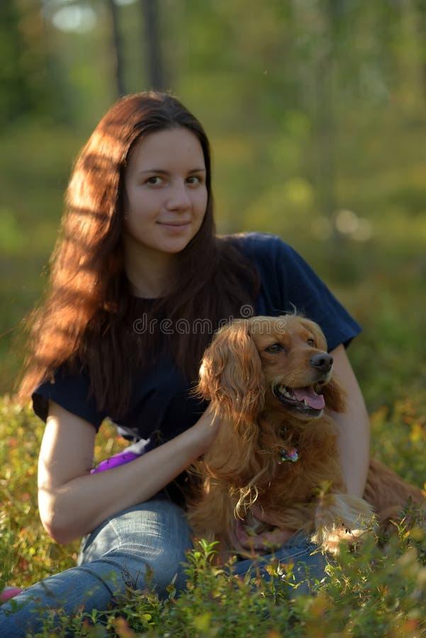 Flicka i skog med hundspanieln arkivbilder