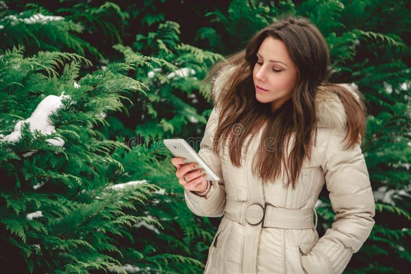 Flicka i skogen som allvarligt ser telefonen royaltyfria foton