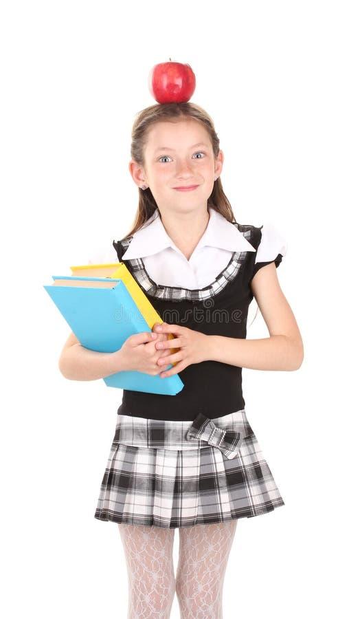 Flicka i skolalikformig med boken och äpplet arkivbild