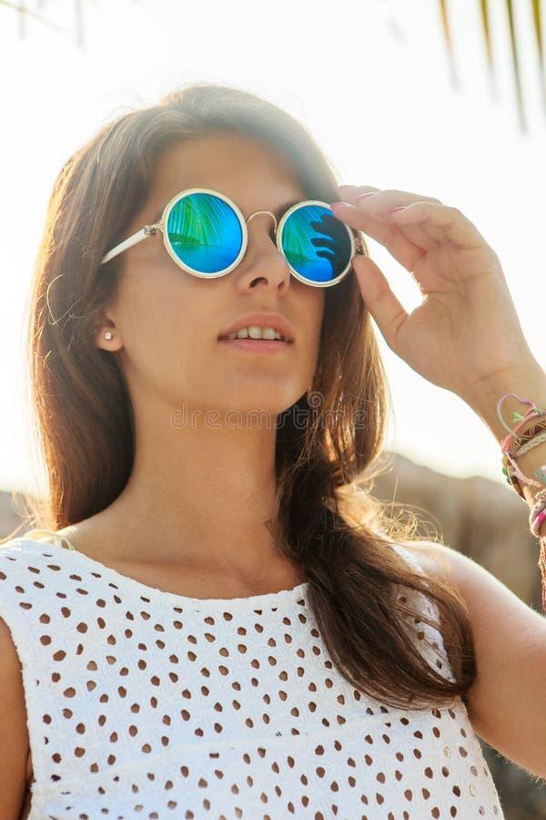 Flicka i solglasögon under solnedgång royaltyfri fotografi