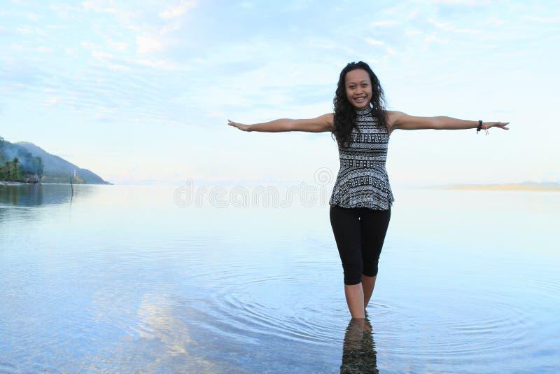 Flicka i soluppgånghavet arkivbild