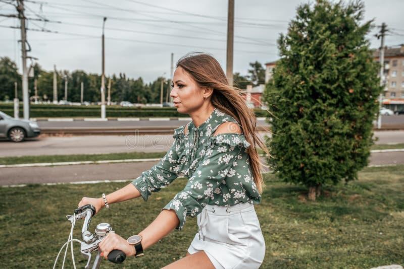 Flicka i sommaren i staden som rider en cykel, mot bakgrunden av träd och gröna bilar I en grön tröja och vit arkivfoto