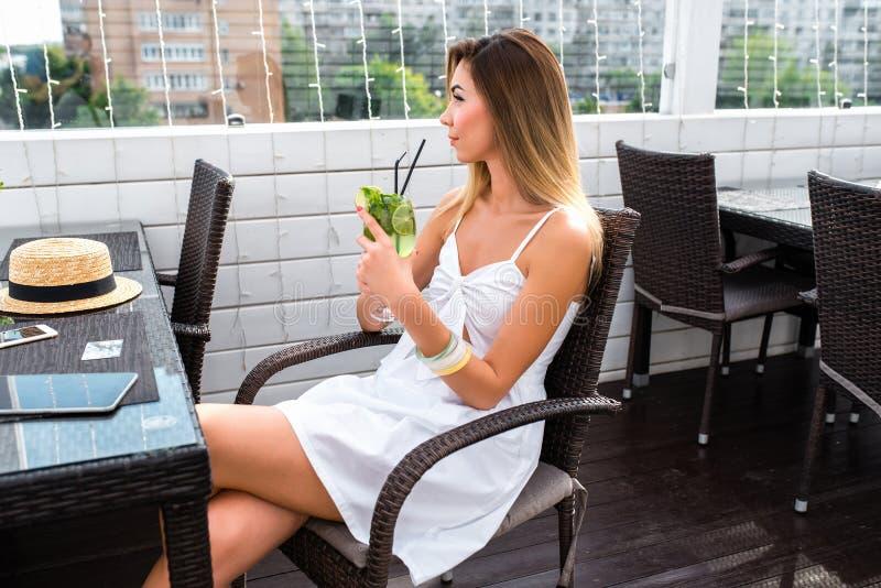 Flicka i sommarkafét som sitter med ett exponeringsglas av coctailen Drömma tankar, lyckligt se som vilar efter en hård dagsverk royaltyfria foton