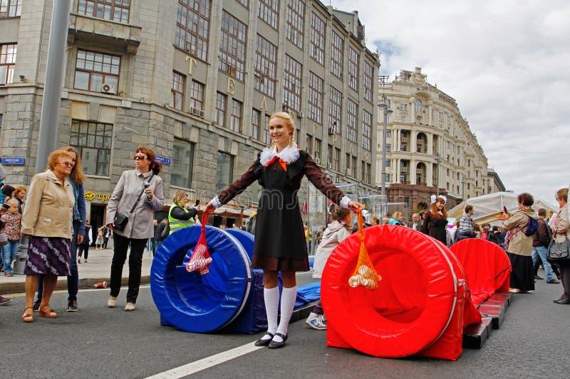 Flicka i sovjetisk skolalikformig och med radpåsar som väntar på ` för start för spelare` gladlynt på den Tverskaya gatan på stad royaltyfri bild