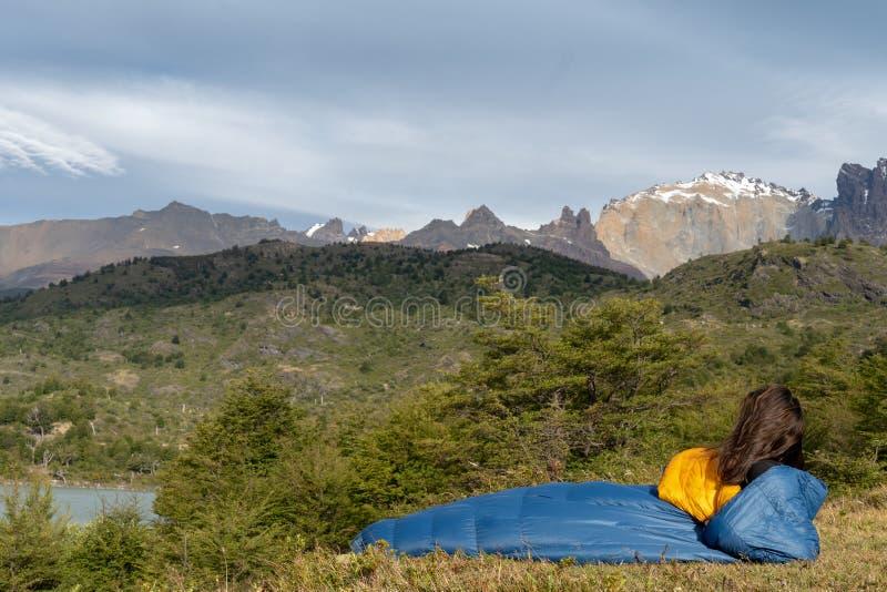 Flicka i sovsäck i berg nära sjön royaltyfria bilder