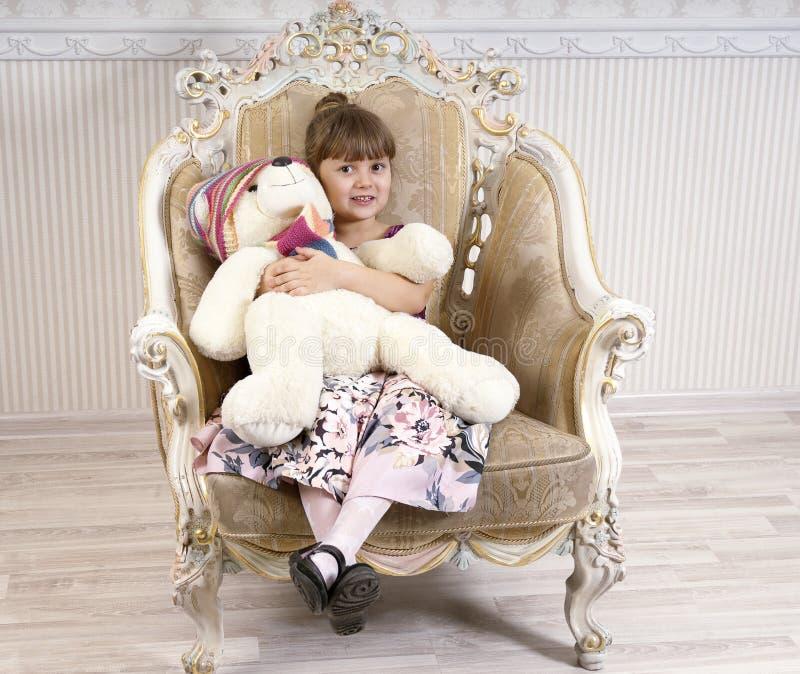 Flicka i stol med en björn royaltyfri bild