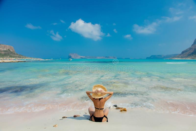 Flicka i svart bikini och med hatten på den Balos stranden royaltyfri foto