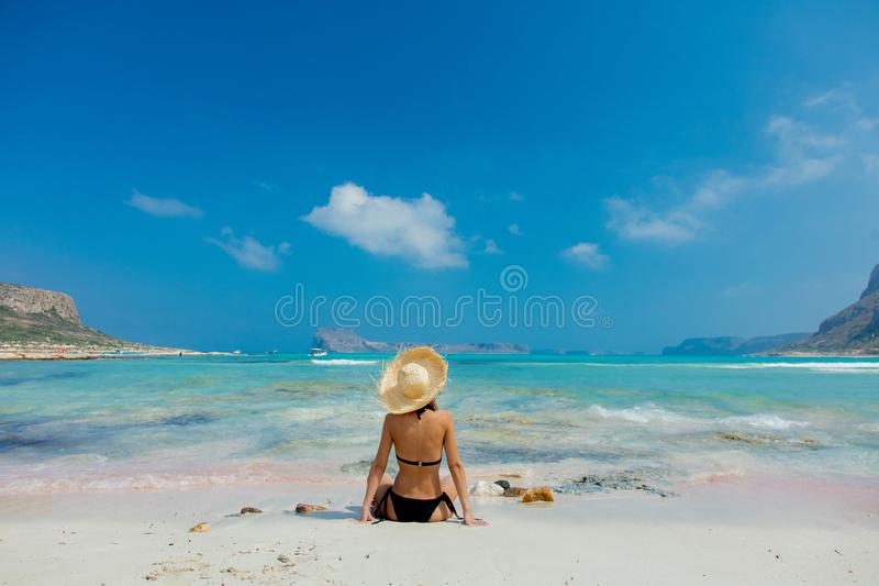 Flicka i svart bikini och med hatten på den Balos stranden royaltyfri fotografi