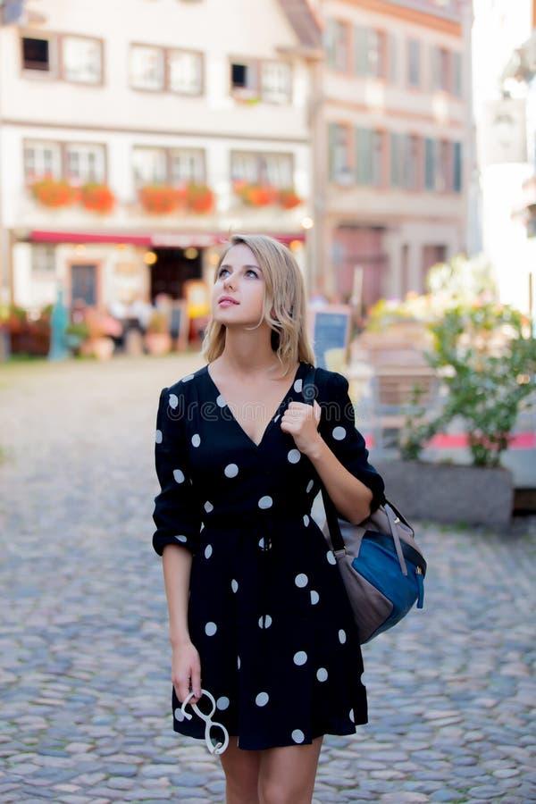 Flicka i svart klänning som går ner gatan i Strasbourg fotografering för bildbyråer