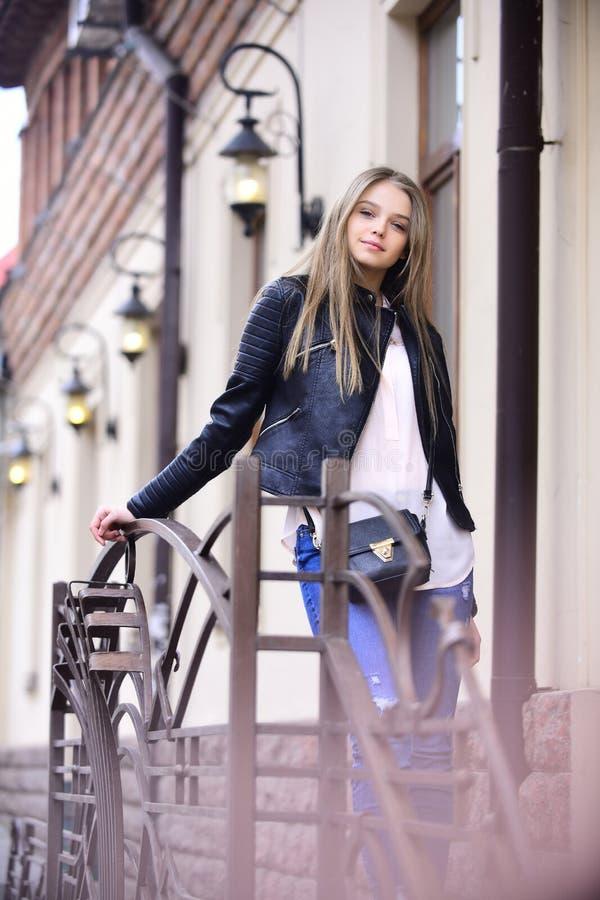 Flicka i tillfällig kläder som är utomhus- på järnstaketet se av flicka nära gatalampor hair long Mode och arkivbild