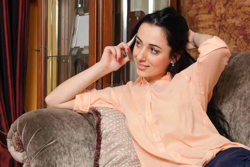 Flicka i tillfällig kläder som talar på telefonen royaltyfri fotografi