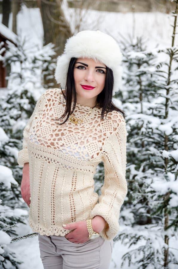 Flicka i varm woolen tröja under snö-täckte trädfilialer fotografering för bildbyråer