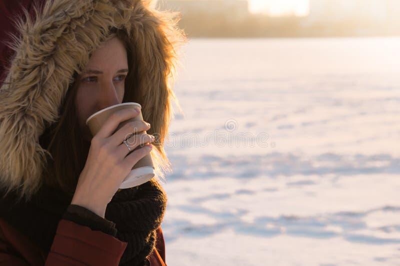 Flicka i varmt lag och huven som har en varm drink på en kall dag arkivbild