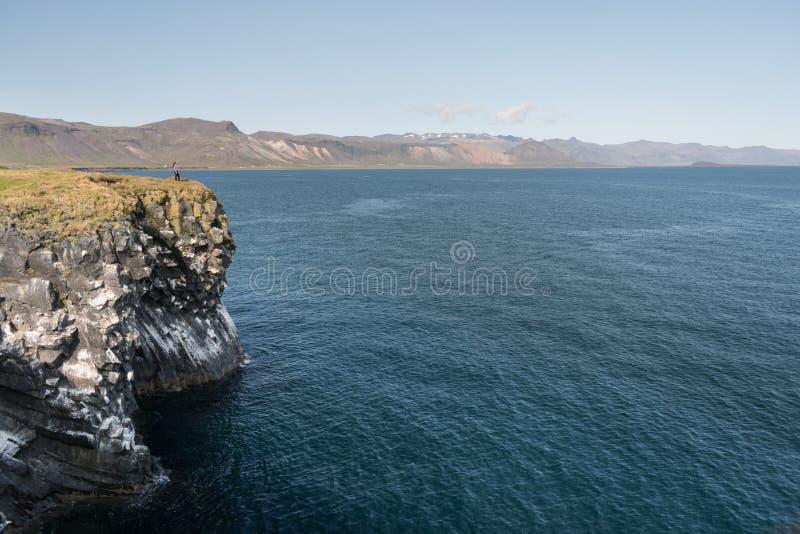 Flicka i vattentäta omslagsställningar på klippan på bakgrund av havet i Island arkivfoto