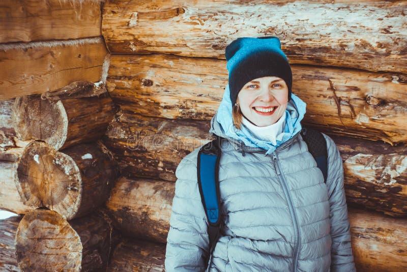 Flicka i vinter i ett trähus arkivbild