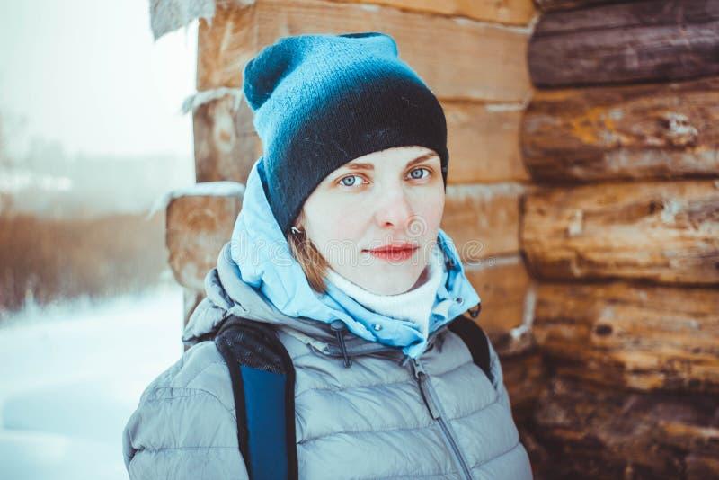Flicka i vinter i ett trähus arkivfoto