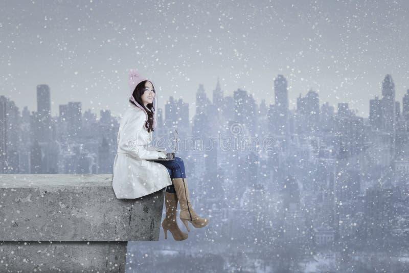 Flicka i vinterlag genom att använda bärbara datorn på taket arkivbilder